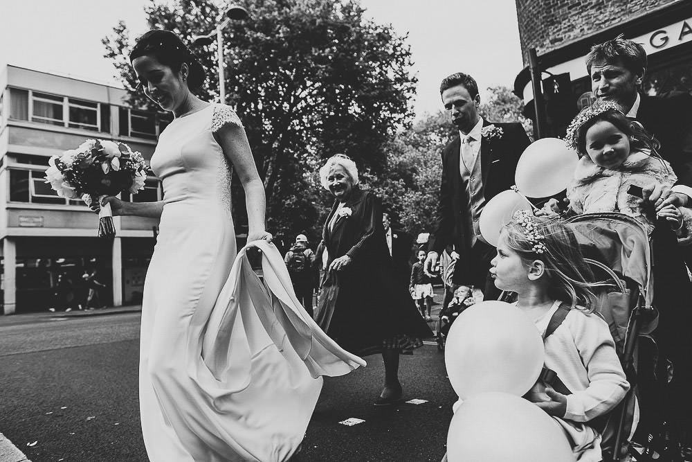 CHELSEA TOWN HALL WEDDING PHOTOGRAPHY BLACK AND WHITE SHOT WEDDING PARTY CROSSING THE ROAD