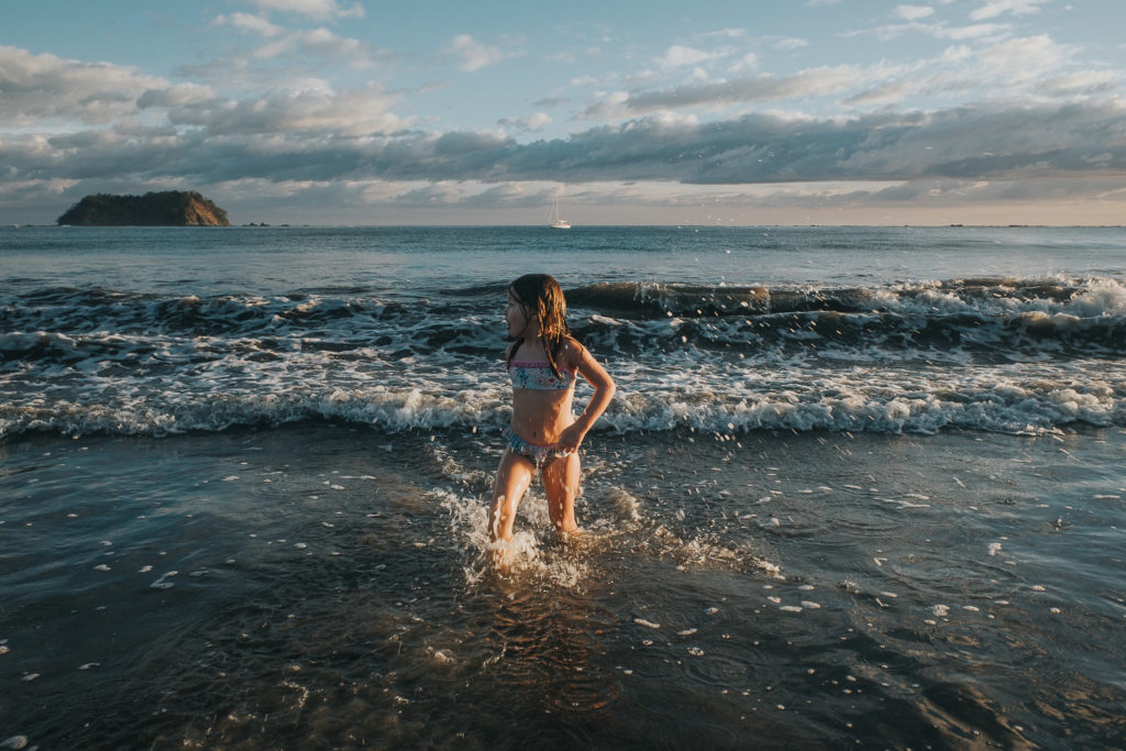 girl splashing in sea at playa samara costa rica wedding photographer
