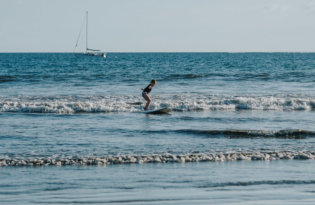 six year old girl surfing at playa samara in costa rica wedding photographer