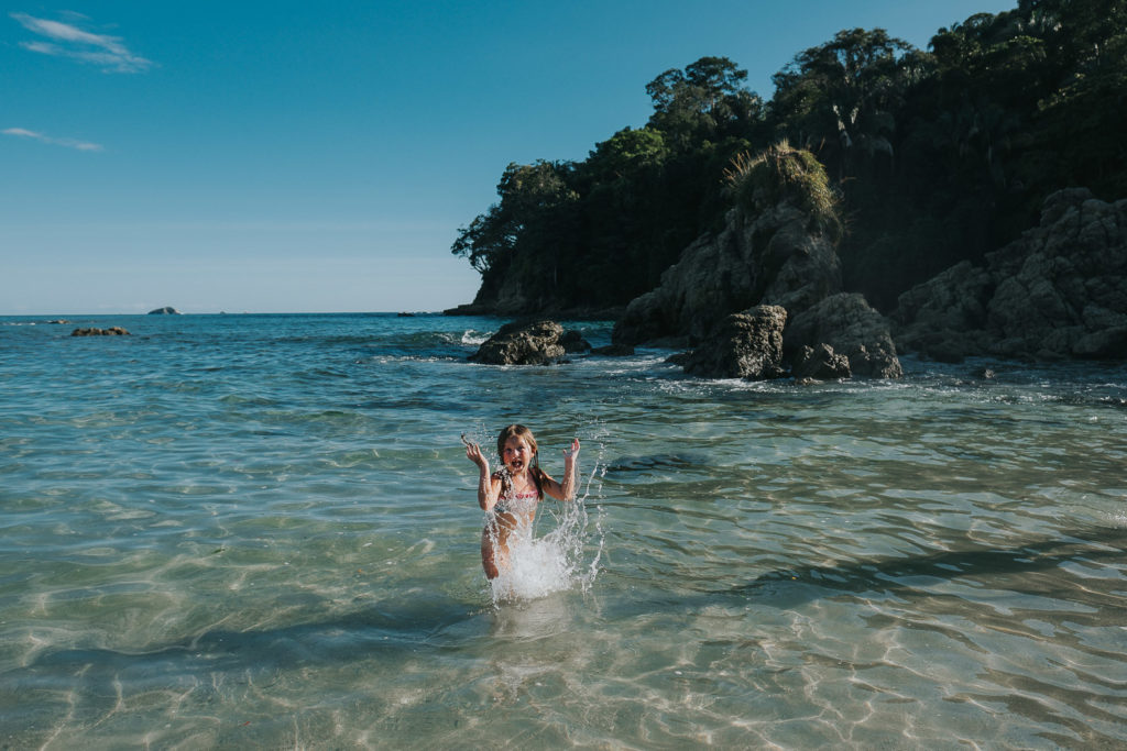 girl splashing in sea at playa manuel antonio costa rica wedding photographer