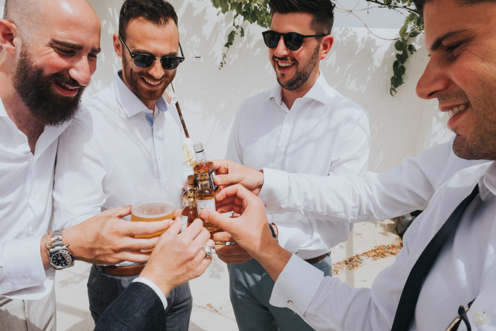 groomsmen drinking whisky shots on sunny terrace jerez wedding photographer