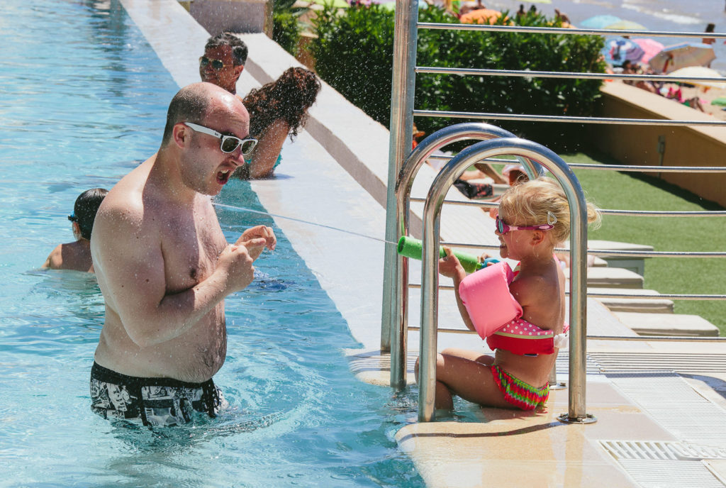 SOL Y MAR CALPE COSTA BLANCA WEDDING PHOTOGRAPHER CHILD WITH WATER PISTOL IN SWIMMING POOL