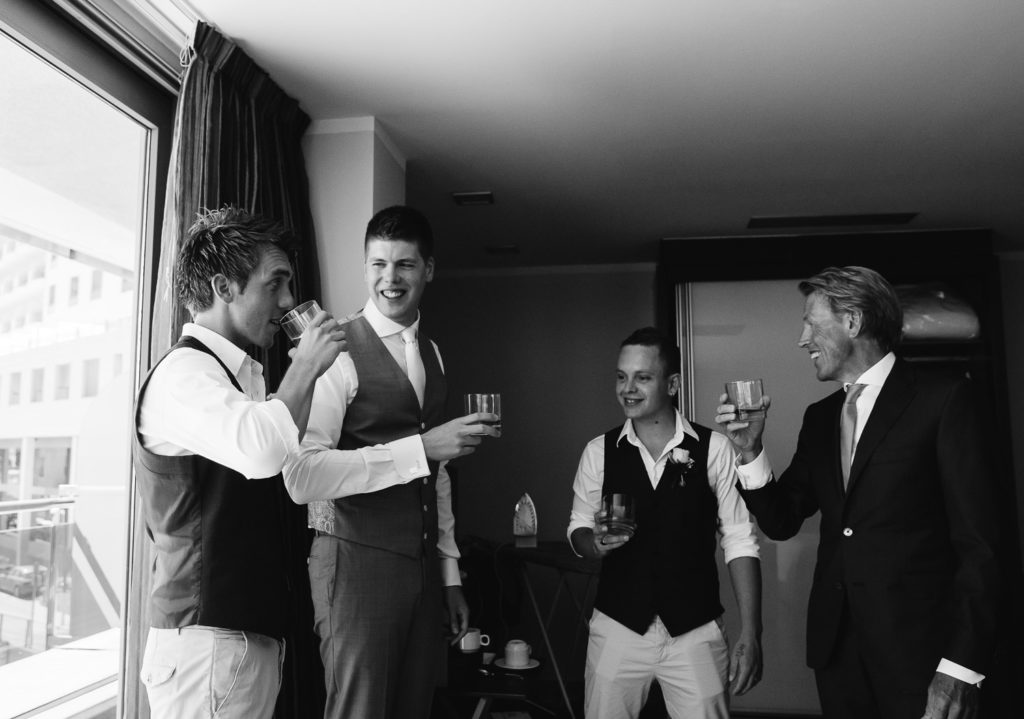 SOL Y MAR CALPE COSTA BLANCA WEDDING PHOTOGRAPHER BLACK AND WHITE GROOMSMEN DRINKING WHISKY TOGETHER