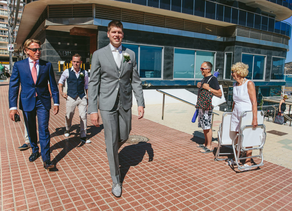 SOL Y MAR CALPE COSTA BLANCA WEDDING PHOTOGRAPHER GROOM AND GROOMSMEN WALKING TO CEREMONY BEACH PEOPLE WATCHING
