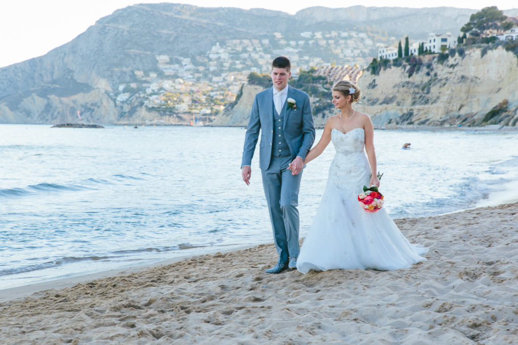 SOL Y MAR CALPE COSTA BLANCA WEDDING PHOTOGRAPHER BRIDE AND GROOM WALKING ON BEACH