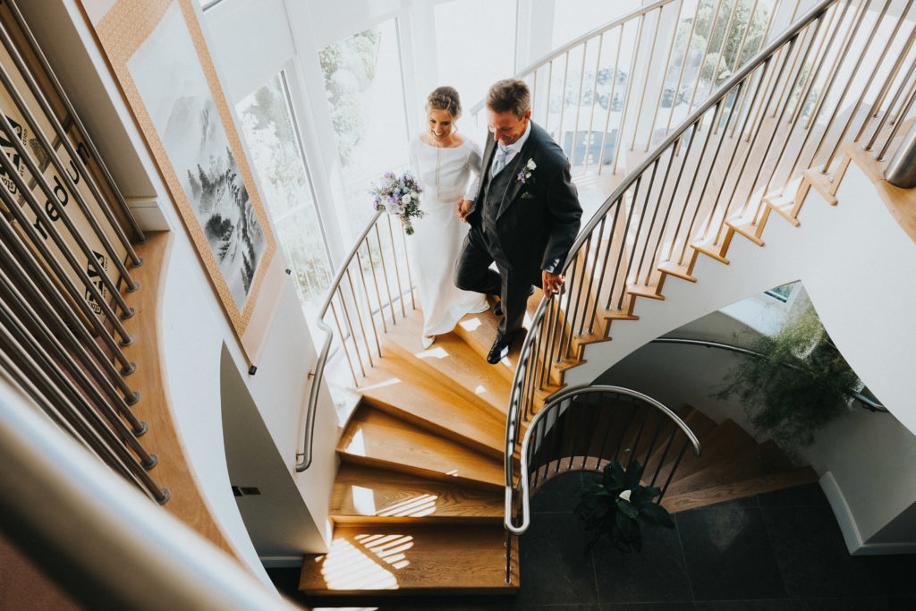 bride and father walking down stairs on wedding morning kent wedding photographer