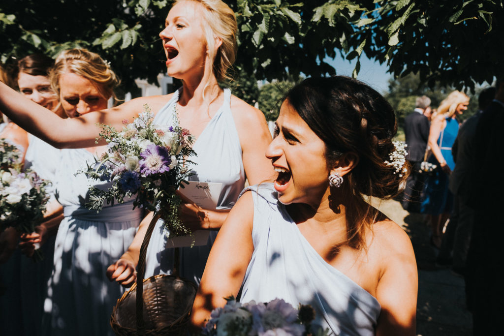 bridesmaids throwing confetti and shouting kent wedding photographer
