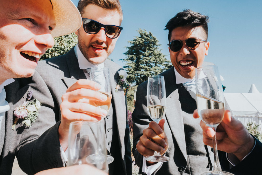 kent wedding photographer wedding guests cheers champagne glasses and laughing