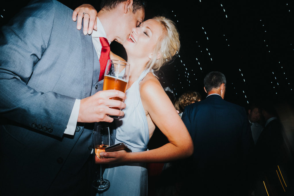 couple at wedding drinking beer on dancefloor kent wedding photographer