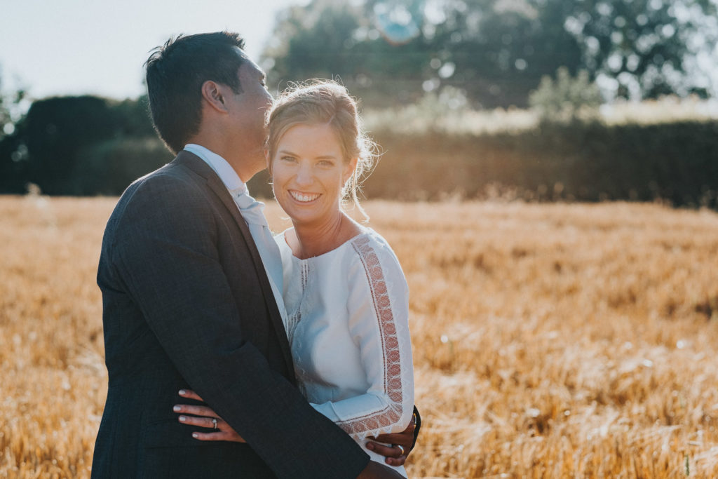 kent wedding photographer bride and groom in wheat field sun flare posing wedding photos