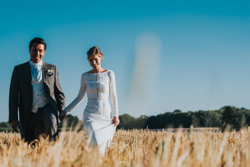 kent wedding photographer bride and groom walking through wheat field in summer blue sky