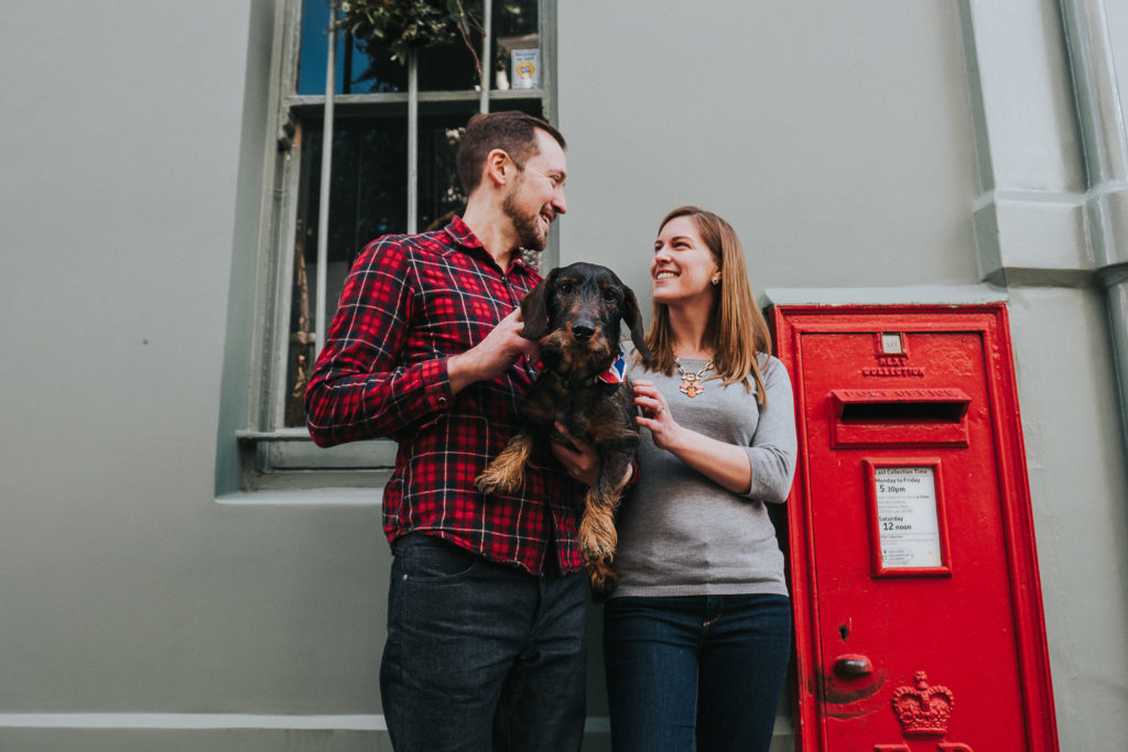COUPLE WITH SAUSAGE DOG BY RED POST BOX LONDON PHOTO SHOOT